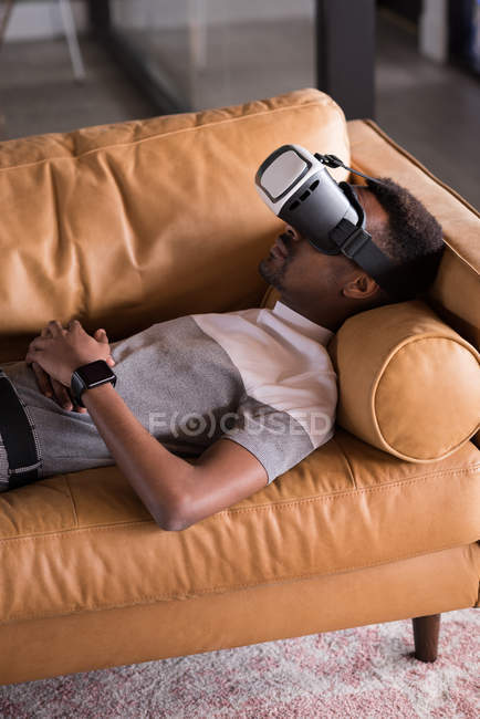 Young man experiencing VR headset while lying on sofa — Stock Photo