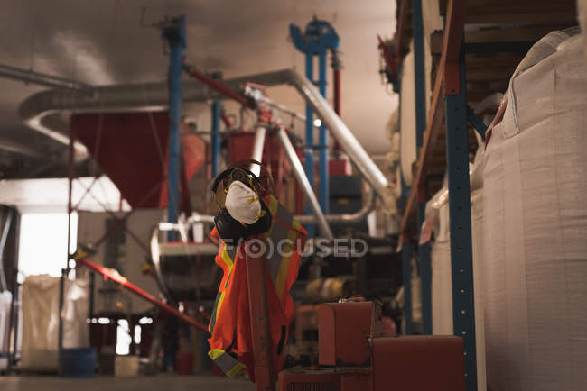 Protective workwear hanging on pole in factory — Stock Photo