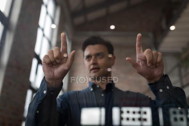 Geschäftsmann mit unsichtbarem Bildschirm im Büro. — Stockfoto