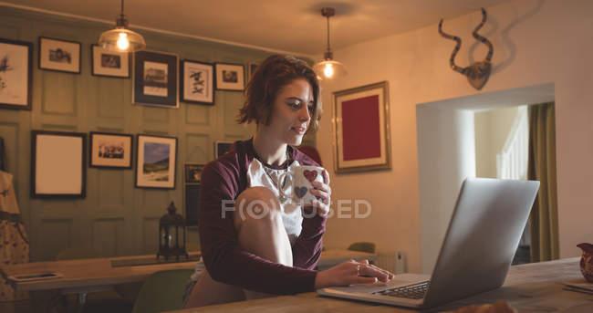 Donna che usa il computer portatile mentre prende il caffè a casa . — Foto stock