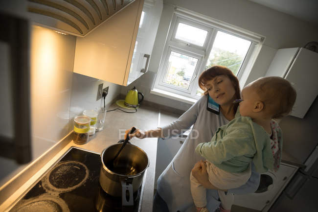 Mother talking on mobile phone while holding her baby girl in the kitchen at home — Stock Photo
