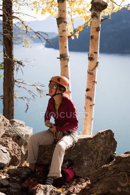 Rock climber sitting on the rock near lakeside — Stock Photo
