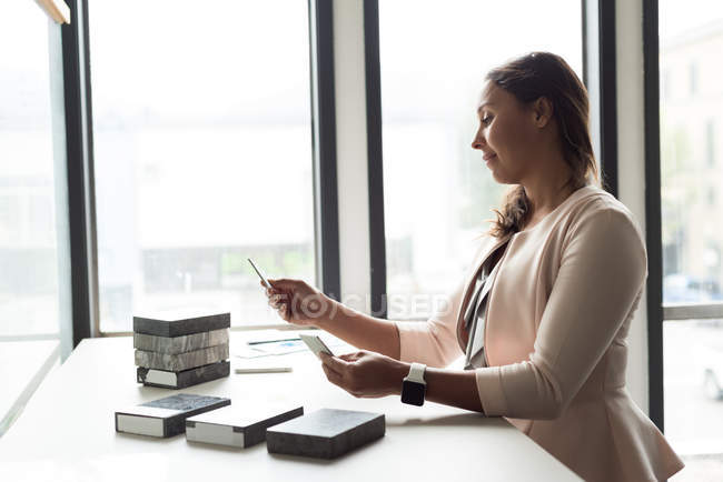 Female executive examining slabs at desk in office — Stock Photo