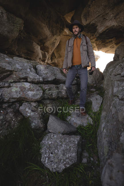 Hiker walking down on rocks in the cave — Stock Photo