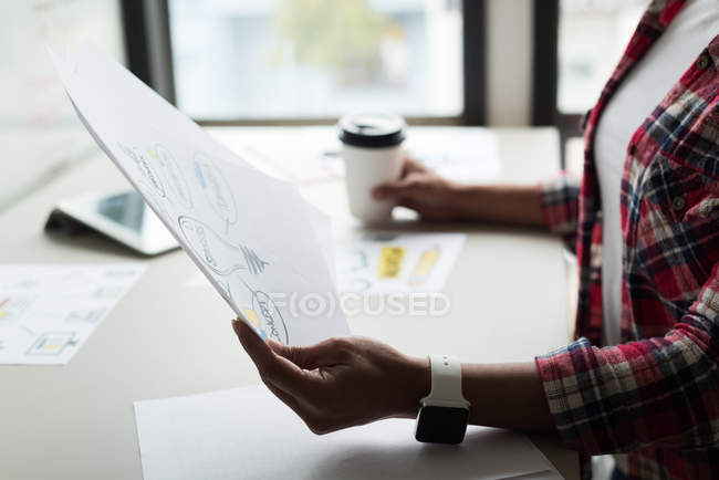 Female executive looking at document in office — Stock Photo