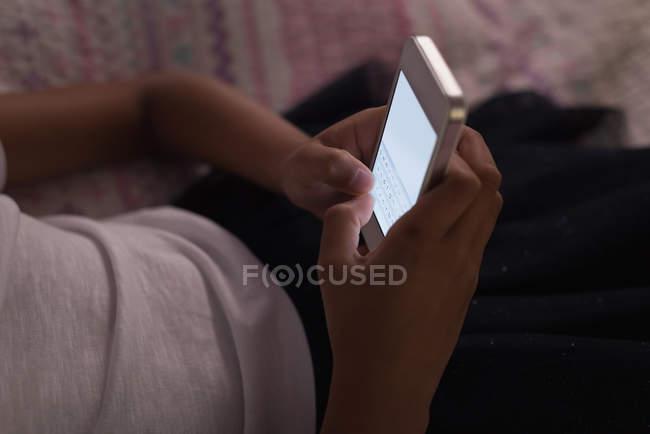 Menina usando telefone celular no quarto em casa — Fotografia de Stock