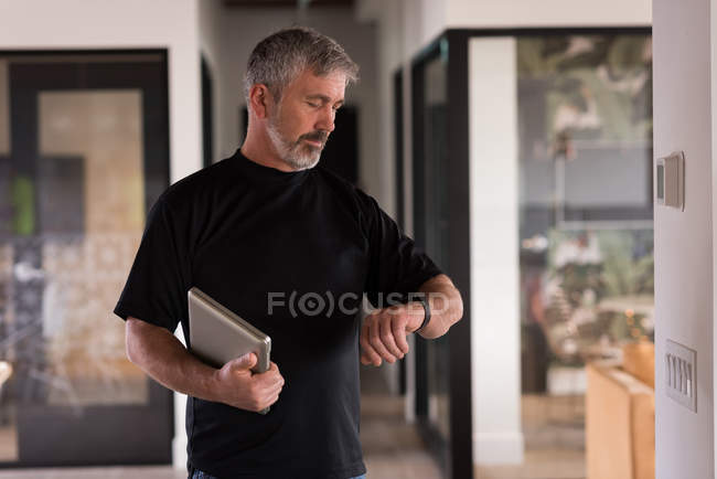Male office executive with laptop checking time in smartwatch at creative office — Stock Photo