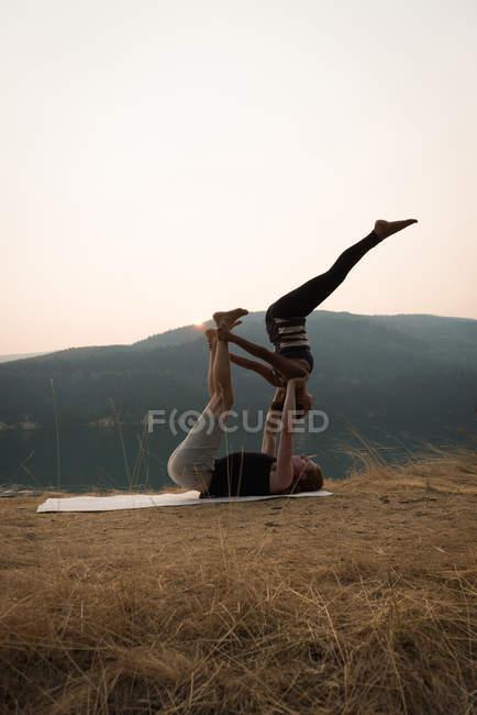 S'adapter couple pratiquant l'acro yoga dans un terrain vert luxuriant au moment de l'aube — Photo de stock