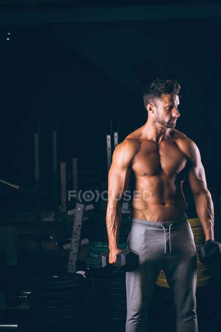 Hombre musculoso haciendo ejercicio con pesas en el gimnasio - foto de stock