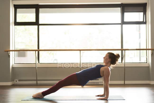 Женщина практикует йогу на тренажерном коврике в фитнес-студии . — стоковое фото