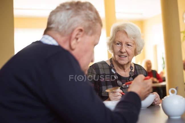 Smiling senior friends interacting while having breakfast at nursing home — Stock Photo