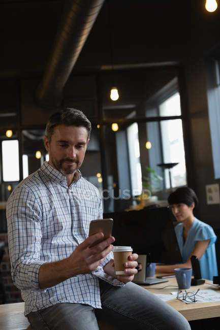 Male executive using mobile phone while having coffee in office. — Stock Photo