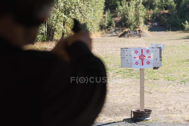 Seção intermediária do homem apontando a arma no alvo no tiro ao alvo — Fotografia de Stock