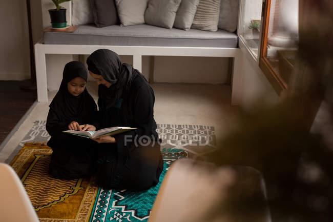 Мусульманская мать помогает дочери читать священный Коран дома — стоковое фото