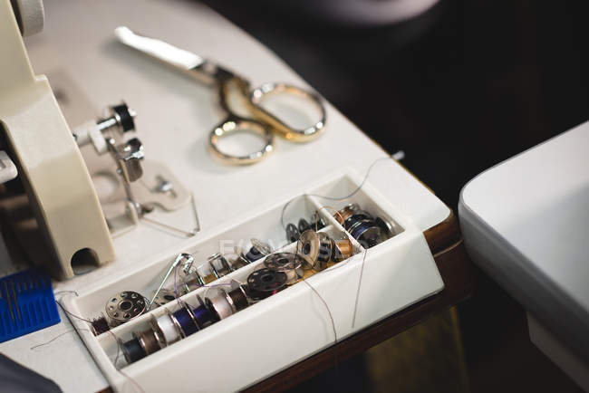 Scissors and thread reel kept near sewing machine at tailor workshop — Stock Photo