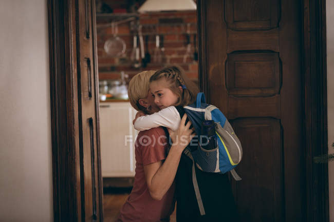 Mother and daughter embracing each other at home — Stock Photo