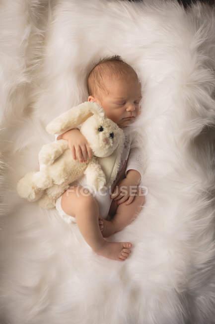 Новорожденный ребенок спать с кролик игрушка на пушистый одеяло. — стоковое фото