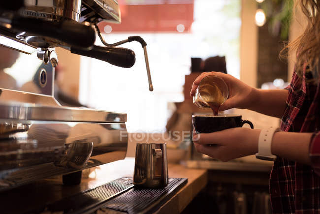Mid section of barista pouring coffee in cup at cafe — Stock Photo