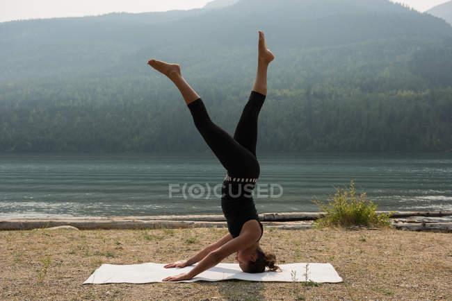 Спортивная женщина практикующая голову стоять у берега моря в солнечный день — стоковое фото