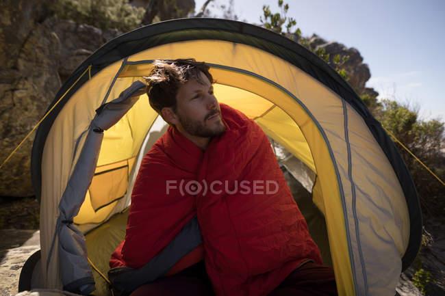 Randonneur enveloppé dans une couverture assis dans une tente par une journée ensoleillée — Photo de stock
