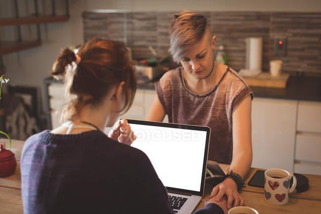 Casal de lésbicas usando laptop e de mãos dadas em casa . — Fotografia de Stock