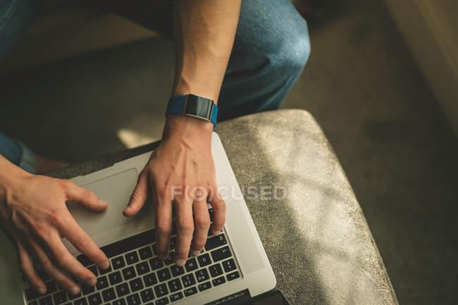 Primer plano de las manos masculinas utilizando el ordenador portátil en la mesa a la luz del sol . - foto de stock