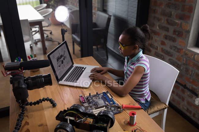 Chica blogger preadolescentes mediante ordenador portátil mientras se suelda el circuito de coches eléctricos del juguete en la oficina. - foto de stock