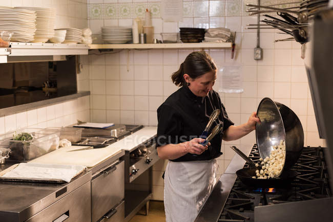 Female chef cooking in the commercial kitchen — Stock Photo