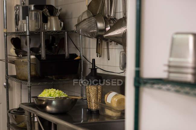 Verduras picadas mantenidas en un colador en la cocina comercial - foto de stock