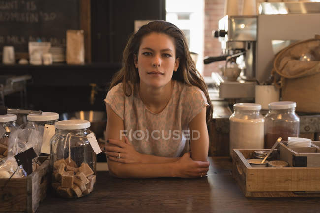 Portrait of waitress standing at counter in the coffee shop — Stock Photo