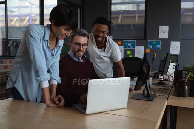 Führungskräfte diskutieren über Laptop am Schreibtisch im Büro. — Stockfoto