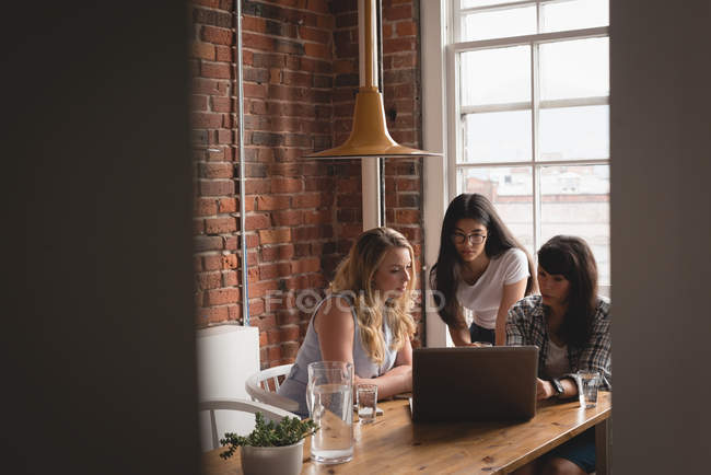Female executives discussing over laptop with each other in the creative office — Stock Photo