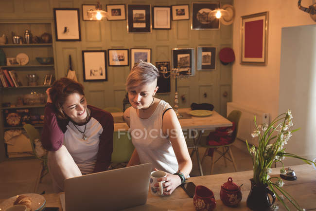 Lesbian couple using laptop at table in living room at home. — Stock Photo