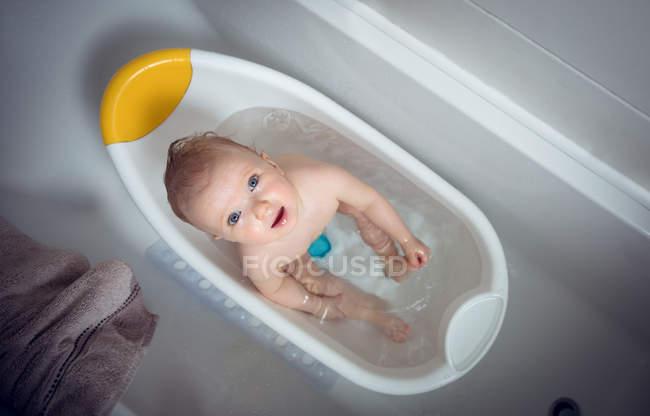 Baby girl taking bath in bathtub at bathroom — Stock Photo