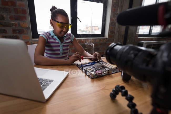 Chica blogger pre-adolescentes para soldar circuitos de coche de juguete eléctrico en oficina. - foto de stock