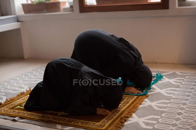 Мусульманська мати і дочка молитися Салят вдома — стокове фото