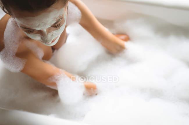 Frau mit Gesichtsmaske badet zu Hause mit Schaum, Nahaufnahme. — Stockfoto