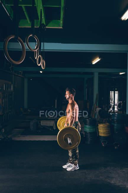 Hombre musculoso haciendo ejercicio con barra de pesas en el gimnasio - foto de stock
