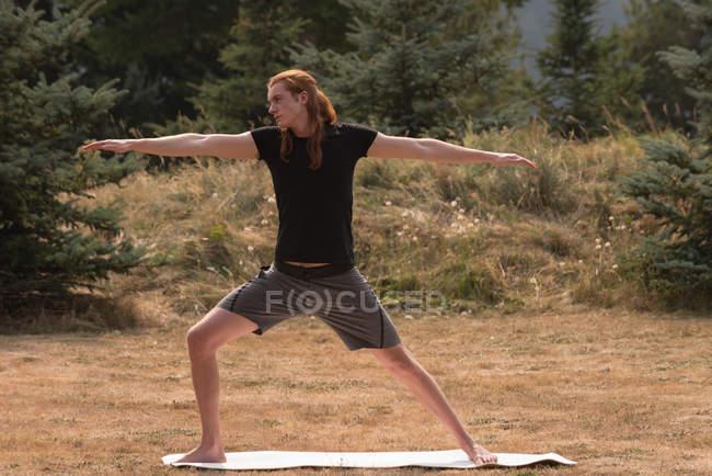 Convient à l'homme effectuant un exercice d'étirement sur un terrain ouvert une journée ensoleillée — Photo de stock