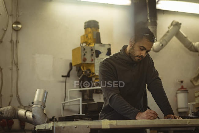 Männliche Arbeiter markieren mit Bleistift in der Fabrik — Stockfoto