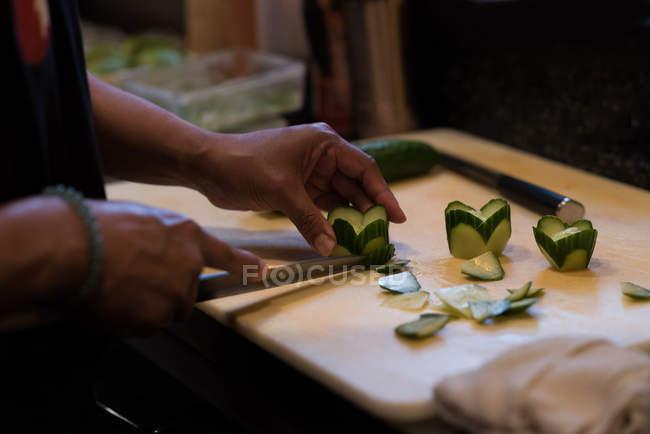 Шеф-повар, нарезания огурцов с deba ножом в ресторане kitchen — стоковое фото