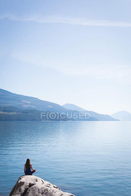 Femme pratiquant le yoga sur le rocher près de la mer — Photo de stock