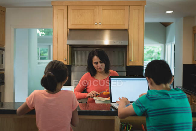 Mother preparing food while kids using digital tablet and laptop in kitchen at home — Stock Photo