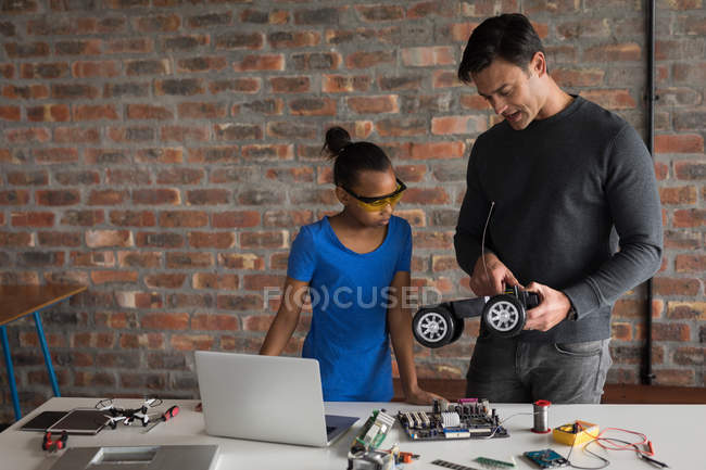 Father explaining daughter about electric model car in office. — Stock Photo