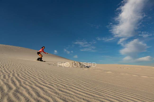 Sandboard femme sur dune de sable au désert — Photo de stock