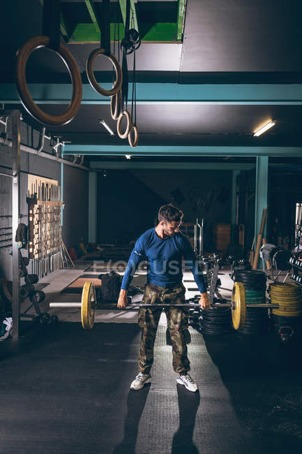Determined muscular man exercising with barbell — Stock Photo