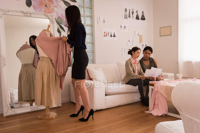 Fashion designer working on mannequin with women talking on sofa. — Stock Photo