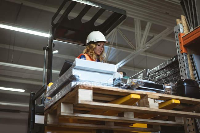 Arbeiterin überprüft Maschinenteil in Fabrik — Stockfoto
