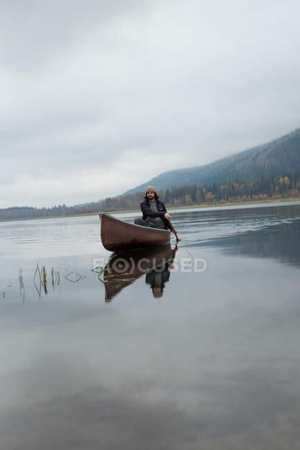 Man oaring canoe in silent river — Stock Photo