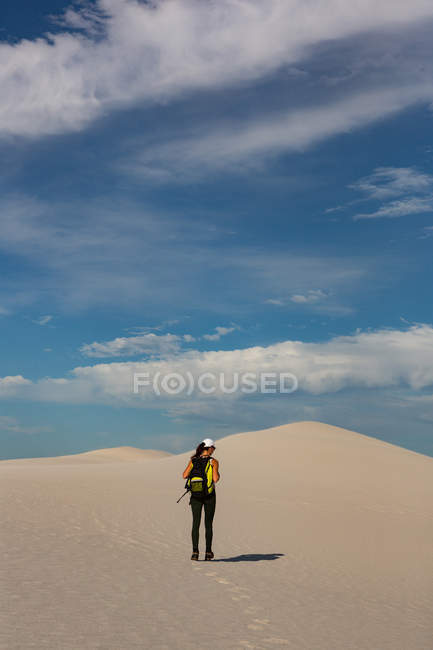 Rear view of female hiker with trekking pole walking on sand — Stock Photo